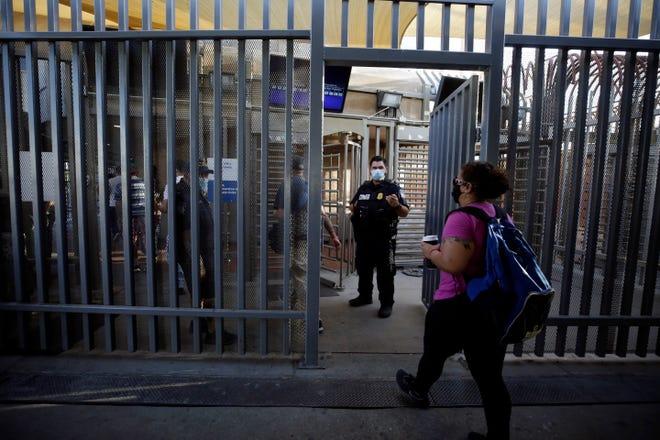 Una mujer cruza caminando la garita frontriza de Calexico, California.