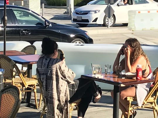 A couple enjoys a drink at a table on Washington Boulevard in Culver City, California Dining areas have been set up on the street, protected from passing cars by water-filled barriers.