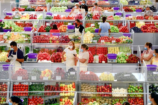 Fruit and vegetable vendors, wearing masks against the spread of the COVID-19 infections, wait for customers at a market in Bucharest, Romania, Tuesday, Aug. 11, 2020.