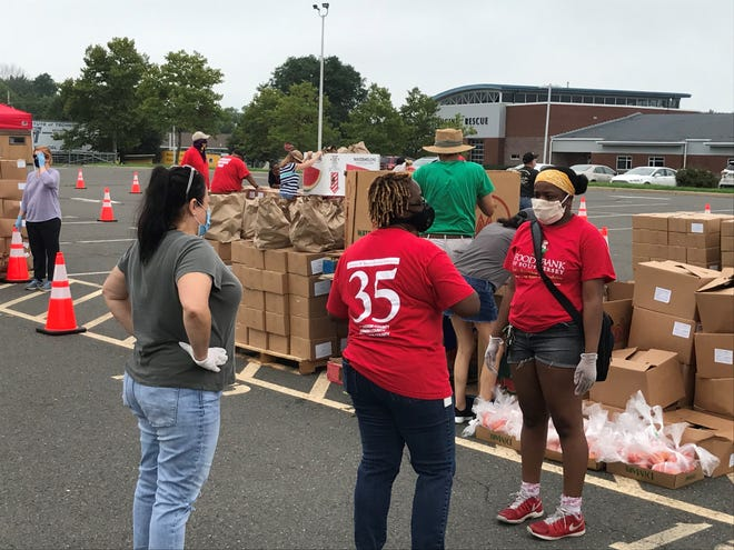 Volunteers figure out their next move during the county's food distribution event in Westampton on Tuesday.