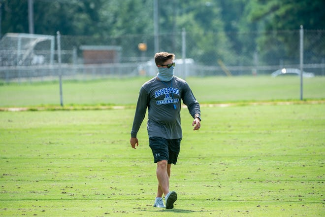 Asheboro head coach Blake Brewer watches his players during their first evening workout last summer. The Blue Comets held their first official practice for the spring 2021 season on Monday. [PJ WARD-BROWN/ THE COURIER-TRIBUNE]