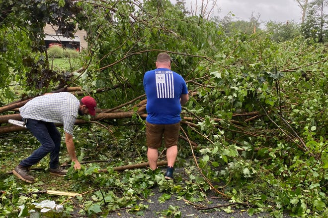 Two people cleanup after Tropical Storm Isaias in a neighborhood near Moore's Lake.