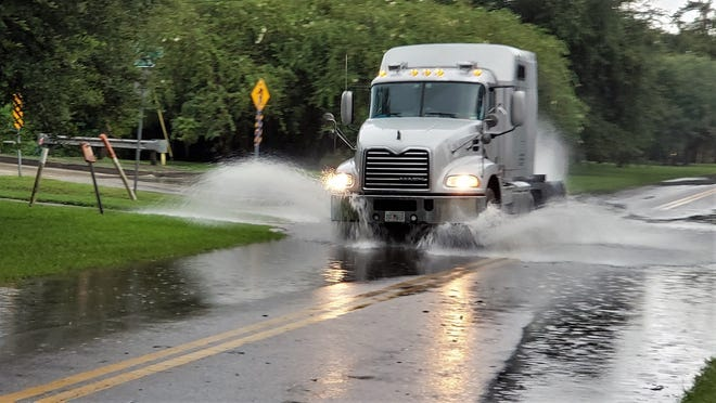 A truck creates a bow wave as it goes through flooding Tuesday night on McCoys Creek Boulevard at King Street. [Dan Scanlan/Florida Times-Union]