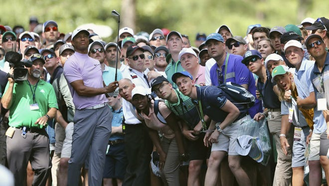 Tiger Woods hits from off the 11th fairway at Augusta National during the first round of the 2019 tournament, with patrons watching the shot. Augusta National decided on Wednesday that it would not admit fans to the tournament Nov. 12-15.