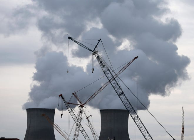 Steam rises from the cooling towers at the Plant Vogtle nuclear power plant in Augusta, Ga., as cranes work to to build two new reactors.