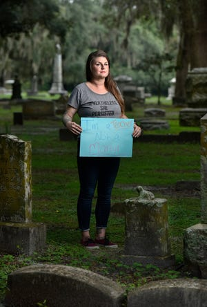"""Whitney Reddick, a Duval County Public Schools special education teacher, holds a sign that says """"I'm a teacher, not a martyr"""" Wednesday at Evergreen Cemetery in Jacksonville. She participated in a march protesting the opening of schools during the pandemic while holding a sign that ended in the cemetery."""