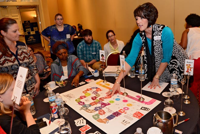"""Rachel White (right), founder of HerSong, explains a board game called """"The Life: The World of Sex Trafficking"""" at the Exchange Club Family Center's annual child abuse and human trafficking prevention conference in 2016. [Bob Mack/Florida Times-Union]"""