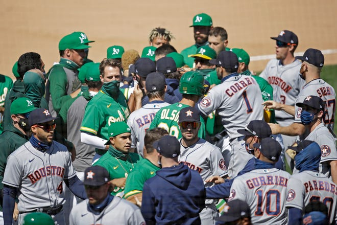Oakland Athletics and Texas Rangers scuffle after Athletics' Ramon Laureano charged the dugout after being hit by a pitch thrown by Astros' Humberto Castellanos during the seventh inning of a baseball game Sunday in Oakland, Calif.