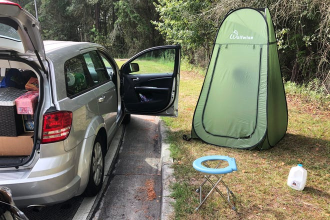 Associated Press editor Michael Warren's car sits next to a fold-out toilet seat and a pop-up changing tent at a rest area along Interstate 75 in Florida. Warren considers these two items essential to long-distance road trips in the pandemic. [MICHAEL WARREN/THE ASSOCIATED PRESS]