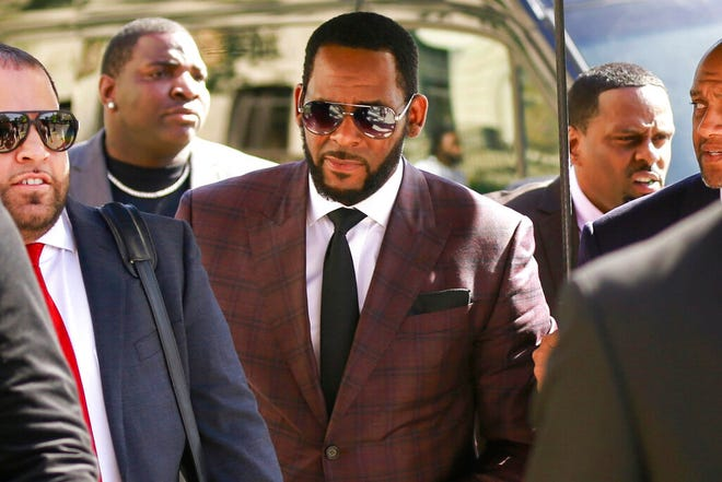 FILE - In this June 26, 2019, file photo, R&B singer R. Kelly, center, arrives at the Leighton Criminal Court building for an arraignment on sex-related felonies in Chicago. Federal prosecutors announced charges Wednesday, Aug. 12, 2020, against three men accused of threatening and intimidating women who have accused Kelly of abuse, including one man suspected of setting fire to a vehicle in Florida.  (AP Photo/Amr Alfiky, File)