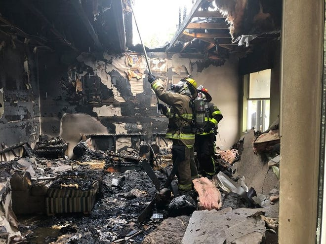 Polk Fire Rescue personnel work the scene of a two-story residential structure fire in north Davenport on Tuesday. [PROVIDED PHOTO/POLK FIRE RESCUE]