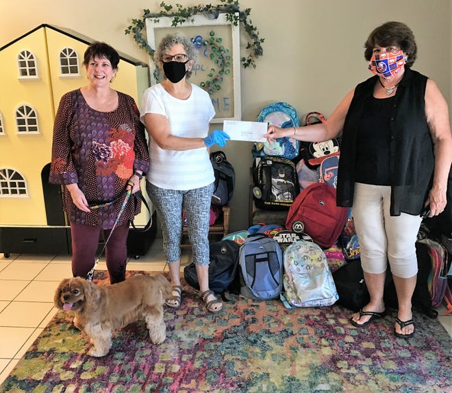 """The Lakewood Ranch Women's Club recently held a Backpack Challenge for HOPE Family Services. From left, Trish Newman, LWRWC philanthropy co-chair with """"ambassador"""" dog Wrigley; and Helene Levin and Cheryl Breining, LWRWC co-presidents. [Photo provided]"""