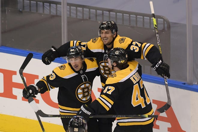 Boston's Patrice Bergeron (37) celebrates with teammates Brad Marchand (63) and Torey Krug (47) after scoring the game-winning goal in a 4-3 victory against the Carolina Hurricanes in the second overtime of Wednesday's Stanley Cup playoff game in Toronto. [Dan Hamilton/USA TODAY Sports]