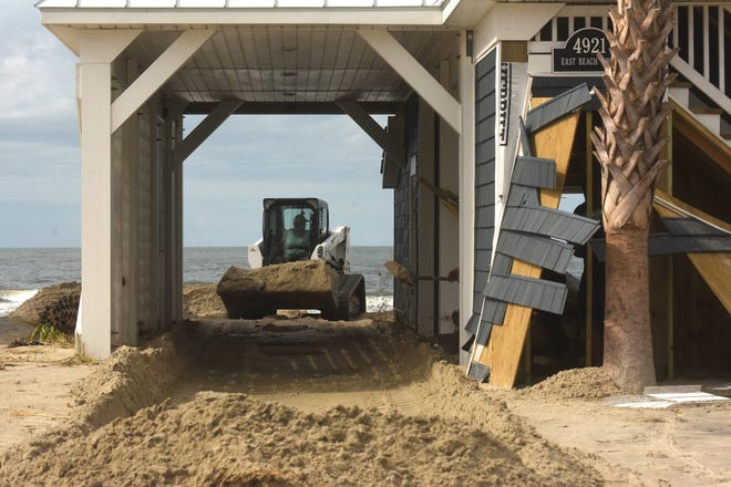 Crews and residents clean up Aug. 5 along Oak Island after Hurricane Isaias.