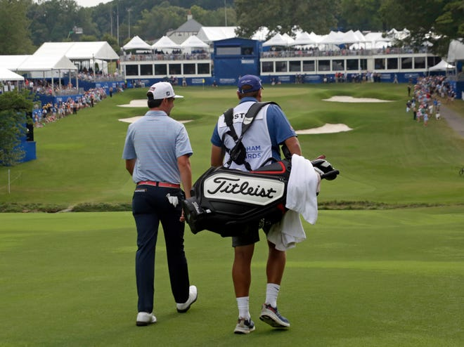 J.T. Poston, left, and caddie Aaron Flener walk down the 18th fairway during the final round of the Wyndham Championship last year.