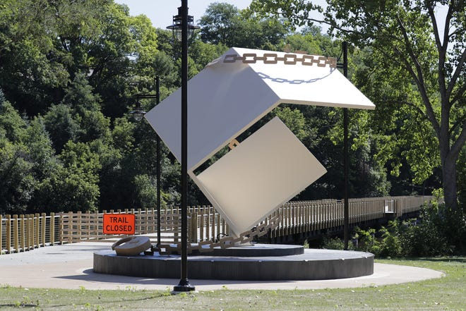 """The newly constructed Lawe Street Trestle Trail in Appleton remains closed while the city waits for an electrical panel needed to operate lights and safety features. The Houdini-inspired """"Metamorphosis"""" artwork stands next to the trail."""