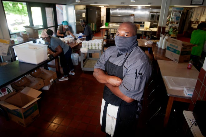 Kikkoman Shaw, head chef of the Southside Kitchen in Asheville, poses for a photo August 12, 2020 as meals are packed by volunteers in the background.