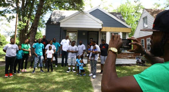 "King Yadee, 35, of Detroit the creator of Th3 Block Development takes a photo of his construction crew on August 5, 2020. Th3 Block Development is a construction company that purchases abandoned houses in Detroit and renovates them with the goal of ""buy back the hood."" Crew members train young people on how to fix homes and about homeownership. He owns three homes between Archdale Street and Vassar Drive that are currently being renovated."