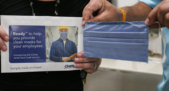 A staff member at Friendship Learning Center in North Fond du Lac holds a Cintas mask that will be provided to school district employees, and cleaned by Cintas, a company that provides a face mask rental service.