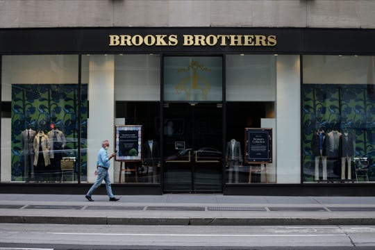 Pedestrians wearing protective masks walk past a Brooks Brothers location in a July 8, 2020 file photo, in New York.