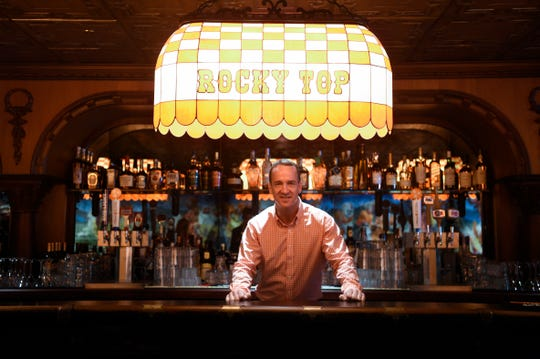 Peyton Manning poses for a photo behind the bar at the new Saloon 16 at the new University of Tennessee-themed Graduate Hotel located at 1706 Cumberland Ave. in Knoxville, Wednesday, August 12, 2020.