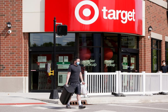 A man walks across Northwestern Avenue after shopping at Target, Wednesday, Aug. 12, 2020 in West Lafayette.