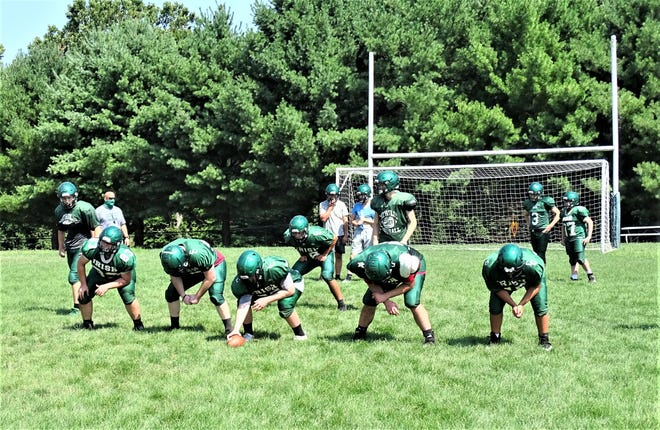 First-year Fisher Catholic coach Luke Thimmes (far left) watches as his team prepares to run a play during a recent practice.