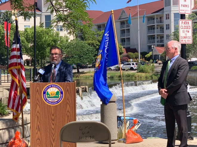 Against the backdrop of Waukesha's Fox River dam, EPA Administrator Andrew Wheeler (left) and Mayor Shawn Reilly present information Aug. 12 about the the agency's $137 million loan, which officials say will save Waukesha Water Utility customers $1 million annually. The loan was made possible by the federal Water Infrastructure Finance and Innovation Act.