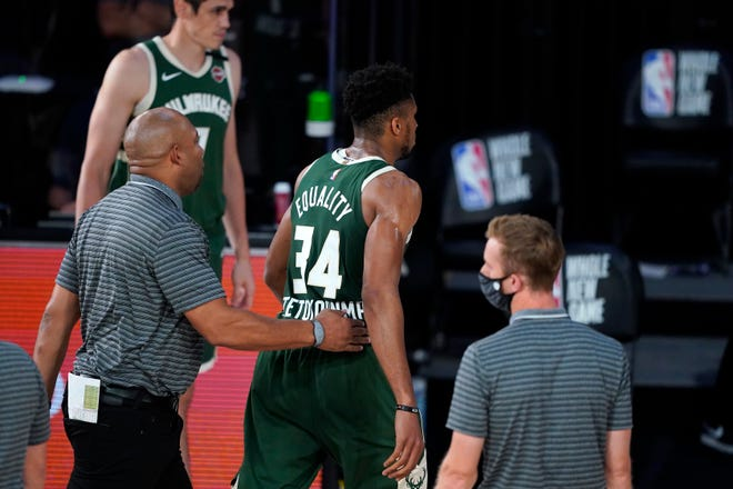 Giannis Antetokounmpo heads to the locker room after being ejected Tuesday night for headbutting Washington's Moritz Wagner.