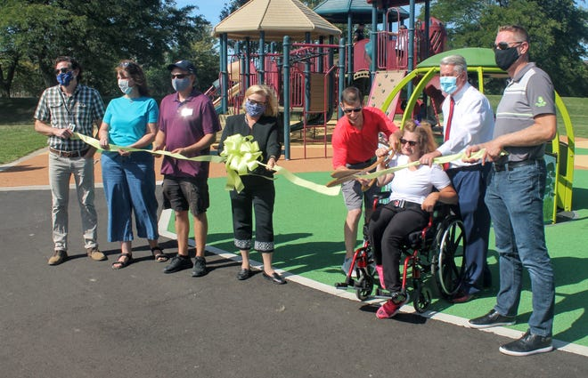 A ribbon cutting takes place Aug. 11 at Heritage Park in Canton for the new playground equipment: a new We-Go-Round and rubber flooring for the playground.