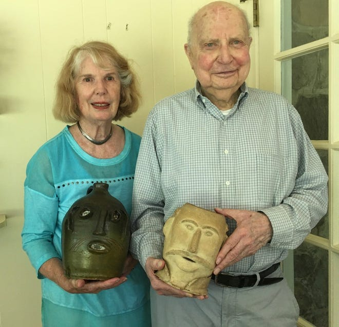 Kay and George Meyer each hold a face jug. The jugs are a distinctive folk art  form made by self taught artists. They have written a book about  their face jugs which have been featured in museum exhibits.