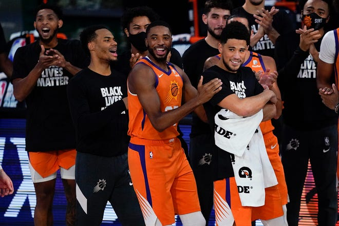 Phoenix Suns players react during player introductions before playing against the Dallas Mavericks during the first half of an NBA basketball game Sunday, Aug. 2, 2020, in Lake Buena Vista, Fla. (AP Photo/Ashley Landis, Pool).