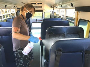 Bus driver Andrea Strege disinfects the inside of a school bus at the Shasta County Office of Education's transportation yard on Grange Street after dropping off students during the first day of school in August 2020.