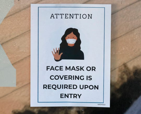 A sign outside a Redding building asks people to put on a mask before going indoors