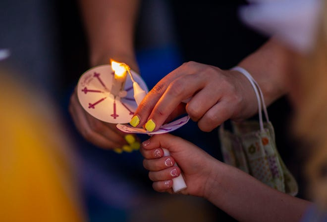 People light candles before lining the roadside for a vigil.