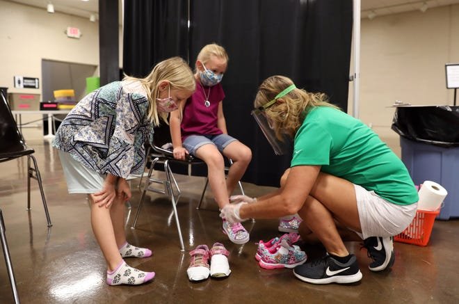Ruby Barnes, left, gets a good look at her sister Ruby's new shoes during the Lace Up for Kids event at Secrest Auditorium on Wednesday. Helping is volunteer Julie Mirgon.