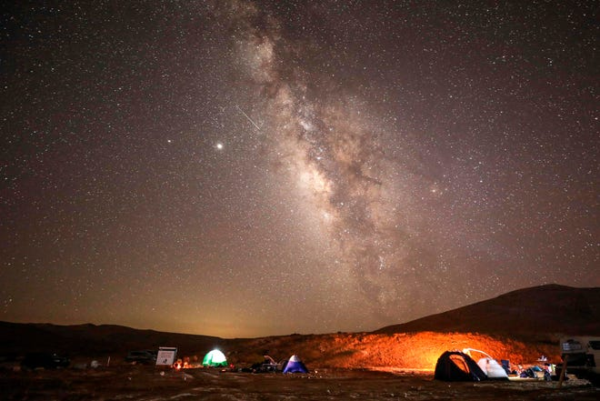 A Perseid meteor streaks across the sky above a camping site at the Negev desert near the city of Mitzpe Ramon on Aug. 11, 2020 during the Perseids meteor shower.