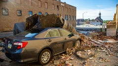 A car is covered in bricks and roofing material in Marshalltown, Iowa, on Tuesday Aug. 11, 2020.