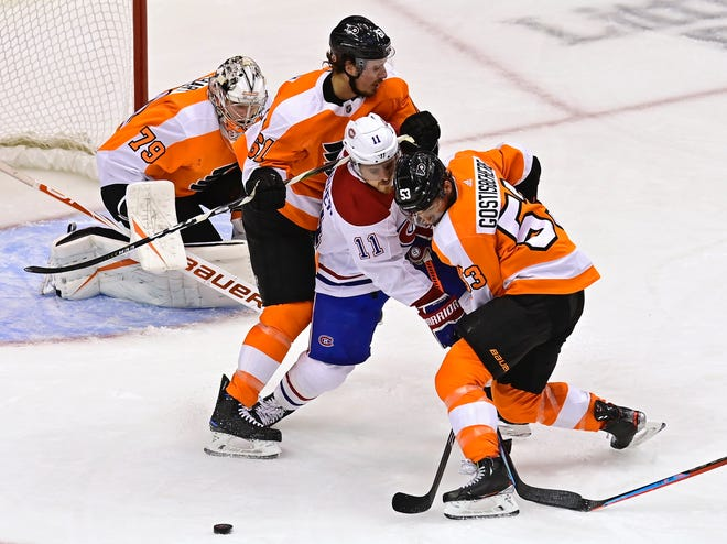 The Flyers' Shayne Gostisbehere, right, and Justin Braun battle the Canadiens' Brendan Gallagher for the puck.