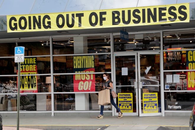 In this Aug. 6, 2020, file photo, a customer leaves a Pier 1 retail store, which is going out of business, during the coronavirus pandemic in Coral Gables. While jobless rates are still at historic highs, Florida's numbers dropped last week more than any other state in the U.S.