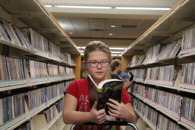 Clover Poland, 11, peruses a book Jan. 4, 2019, while her family members look over the DVD selection at the Burlington Public Library.