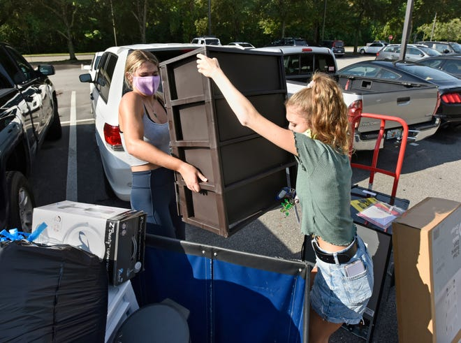 Freshmen students Ashley Campbell (left) and Ashley Hagadorn move furniture into their residence hall room Wednesday at the University of North Florida. The school is allowing a limited number of students at a time to move in because of the coronavirus.  [Will Dickey/Florida Times-Union]