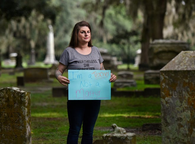"""Whitney Reddick, a Duval County Public Schools special education teacher, holds a sign that says """"I'm a teacher, not a martyr"""" Wednesday at Evergreen Cemetery in Jacksonville. She participated in a march protesting the opening of schools during the pandemic while holding a sign that ended in the cemetery. [Will Dickey/Florida Times-Union]"""