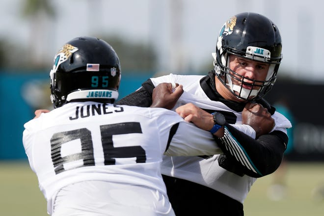 Jacksonville Jaguars defensive linemen Abry Jones, left, and Taven Bryan perform a drill during workouts Wednesday. [JOHN RAOUX/THE ASSOCIATED PRESS]
