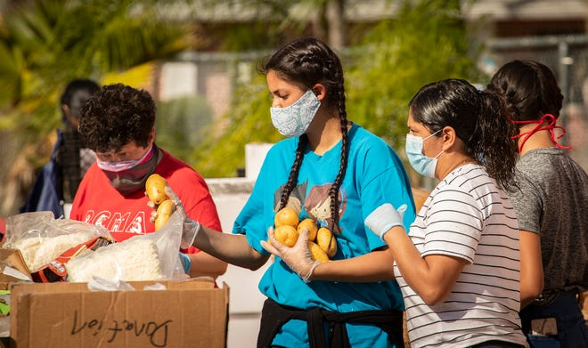 Volunteers prepare food boxes at Redlands Christian Migrant Association to distribute to farmworkers in Mulberry. [ERNST PETERS/THE LEDGER]