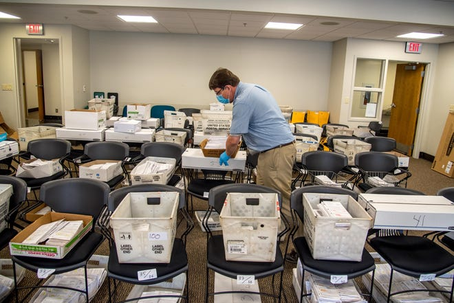 Election official Jim Fortner places a crate of sorted absentee ballots with others from the same ward at the Madison City-County Building on Aug. 5. Delays and failure to deliver absentee ballots in Wisconsin and other key swing states have sparked concerns about how well the November presidential election will be managed during the pandemic.