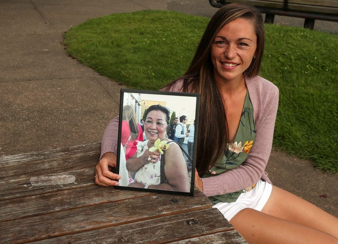"Sarah Milne at Silverdale Waterfront Park on Wednesday with a portrait of her great aunt, who died from COVID-19 last month. Though Milne has not tested positive for COVID-19, she says her family has paid the ""ultimate price"" in the pandemic with the death of a beloved family member."