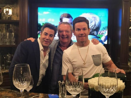 From left: Jay Feldman, restaurant owner Nino Cutraro and Mark Wahlberg gather for dinner at  Cutraro' Bella Piatti restaurant in Birmingham in August 2019. The three were celebrating opening a Wahlburgers restaurant in Royal Oak.