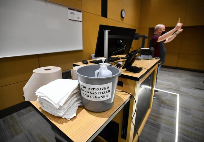 CMU Biology Chair Steve Gorsich in one of the large auditorium class rooms with cloths, towels and disinfectant to clean off tables in between classes in the CMU Biosciences building.