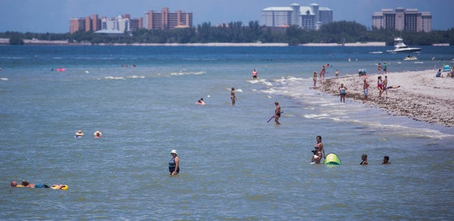 Beachgoers hang out on the on Fort Myers Beach on Thursday, August 13, 2020.